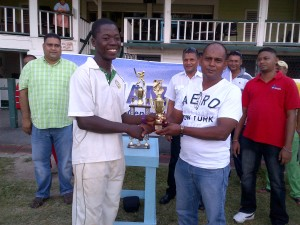 Sherfane Rutherford receiving his man-of-the-match trophy from Junior Selector chairman, Nazimul Drepaul