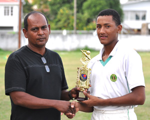 Kemol Savory (right) collects his man-of-the-match award from the chairman of the DCB junior selection committee Nazimul Drepaul.