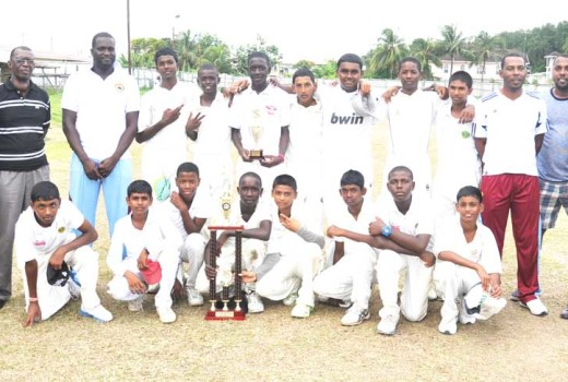Members of the victorious Berbice team display their hardware along side officials of the GCB
