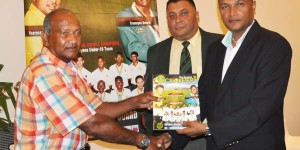 """Alvin Kallicharran (left) accepts a copy of """"The Guyana Cricketer"""" from GCB secretary Anand Sanasie in the presence of Marketing manager Raj Singh"""
