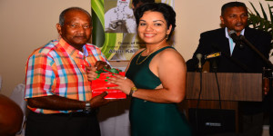Former Guyana and West Indies batsman Alvin Kallicharran is presented with his gift by Assistant Administrator of the GCB Secretariat Ms Melinda Bishundyal. (Samuel Maughn photo)