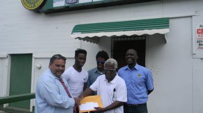 GCB President, Drubahadur, handing over the donation cheque to GuyBCA Executive Member, Cecil Morris