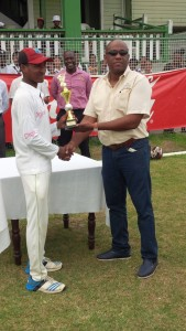Joshua Persaud receiving his man-of-the-match trophy from bran manager of Banks DIH Ltd Rainforest Water