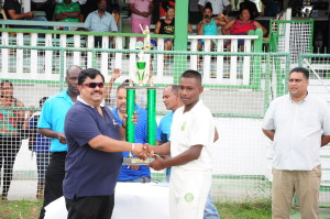 Demerara captain, Sachin Singh, receiving the winning trophy from Dave Narine, proprietor of Dave West Indian Exports GUY/NY
