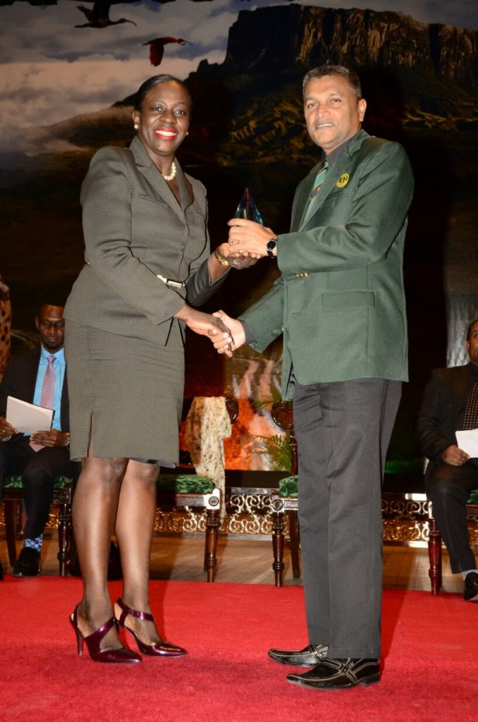 "Anand Sanasie receiving his award for ""Sports Official of the Year 2015"" from Minister responsible for Sports, Nicolette Henry"