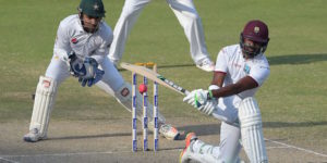 West Indies batsman Darren Bravo (R) plays a shot as Pakistani wicketkeeper Sarfraz Ahmed looks on during the final day of the first day-night Test between Pakistan and the West Indies at the Dubai International Cricket Stadium in the Gulf Emirate on October 17, 2016. / AFP / AAMIR QURESHI        (Photo credit should read AAMIR QURESHI/AFP/Getty Images)